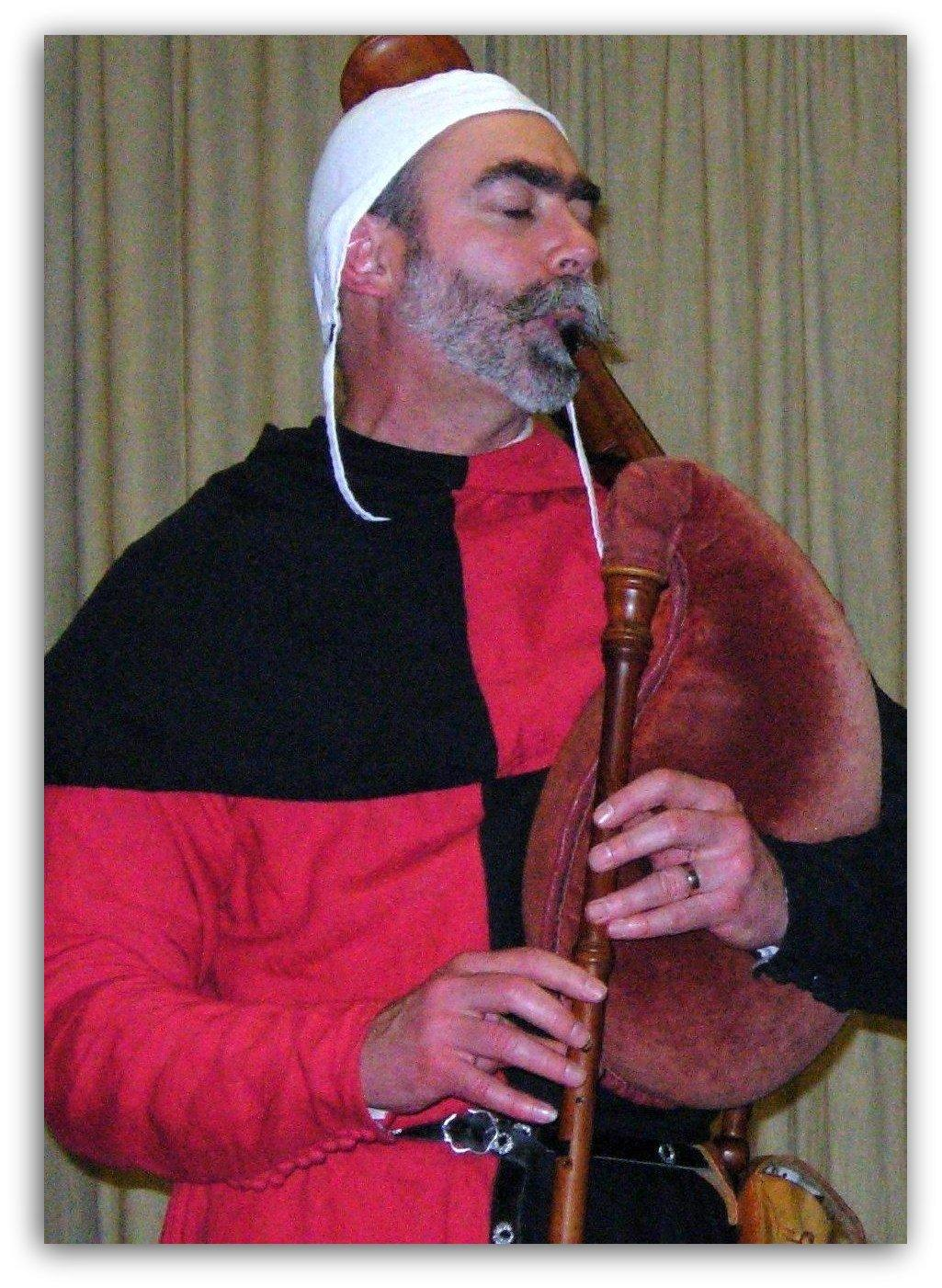 medieval musician entertains guests at banquet
